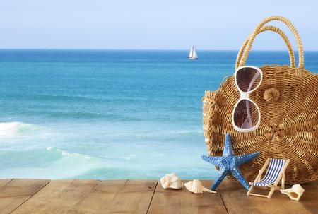 Concepto de vacaciones y verano con objetos de estilo de vida marina sobre una mesa de madera enfrente del fondo del paisaje marino