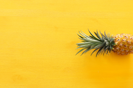 Ripe pineapple over yellow wooden background. Beach and tropical theme. Top view