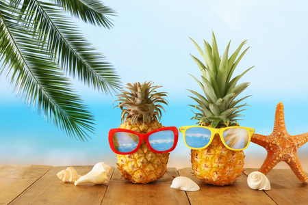 Ripe couple pineapple in stylish sunglasses over wooden table or deck against blue sea, relaxing. Tropical summer vacation concept. Stockfoto