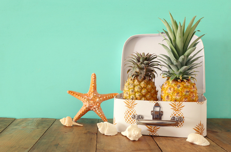 Ripe couple pineapple in suitcase over wooden table or deck. Tropical summer vacation concept
