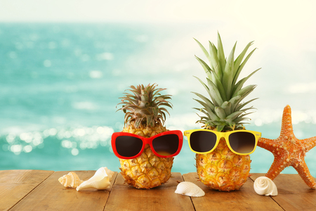 Ripe couple pineapple in stylish sunglasses over wooden table or deck against blue sea, relaxing. Tropical summer vacation concept. Imagens