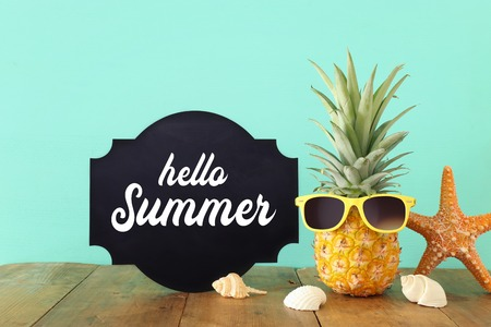 Ripe pineapple in stylish sunglasses over wooden table or deck relaxing. Tropical summer vacation concept
