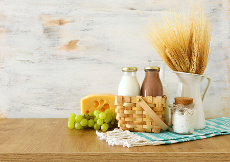 photo of dairy products over wooden table. Symbols of jewish holiday - Shavuot