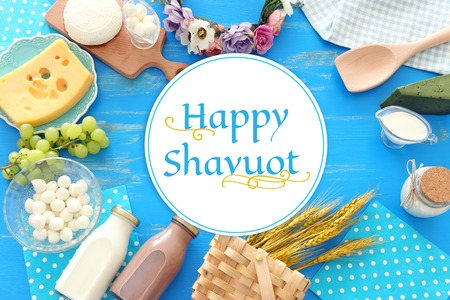 Top view photo of dairy products over blue wooden background. Symbols of Jewish holiday - Shavuot Zdjęcie Seryjne - 122875848