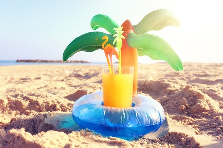 Vacation and summer concept with fresh fruit drink and palm shape pool float over sand at the beach Reklamní fotografie