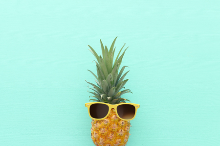 Ripe pineapple in stylish sunglasses over wooden blue background. Tropical summer vacation concept. top vew