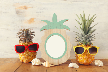 Empty photo frame and couple of funny pineapple with sunglasses. For photography and scrapbook montage Standard-Bild