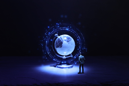 Miniature man looking at Small crystal globe in front of dark and dramatic light. Global issues concept