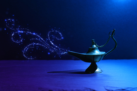 Image of magical mysterious Aladdin lamp with glitter smoke. Dark background and dramatic light Stock Photo