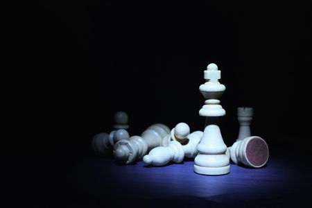 Wooden chess figures under dark and dramatic lighting