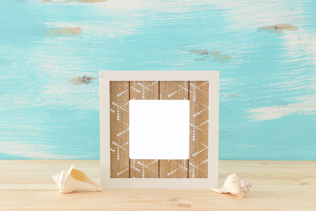 Blank white photo frame and sea shells over wooden table and pastel blue background. Ready for photography montage