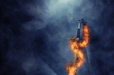 Foto misteriosa y mágica de espada de plata con llamas de fuego sobre fondo negro gótico. Concepto de época medieval