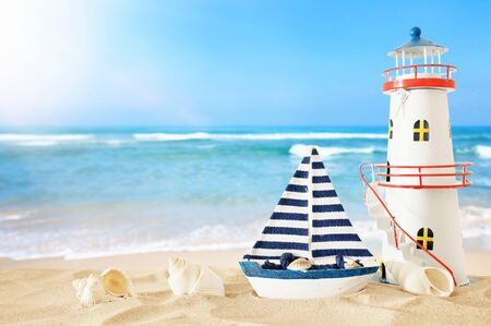 Vintage wooden boat and lighthouse over beach sand and sea landscape background