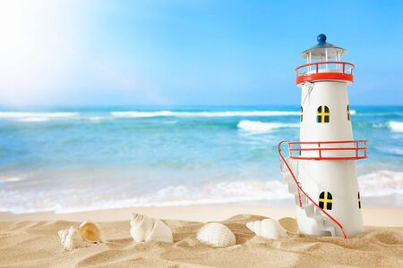 Vacation and summer concept with vintage boat, starfish, lighthouse and seashells over beach sand