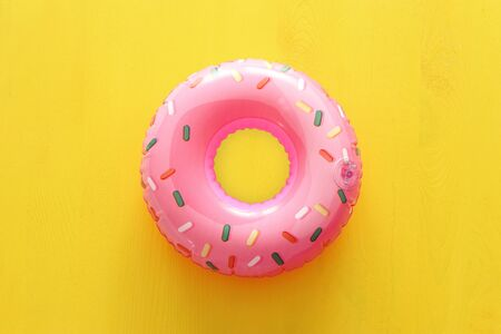 Inflatable donut ring over yellow wooden background