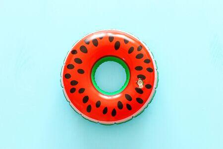 Inflatable watermelon ring over blue wooden background Reklamní fotografie