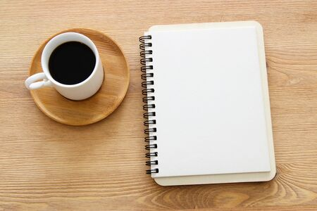 Open notebook with empty pages over wooden old office desk table. Top view, flat lay