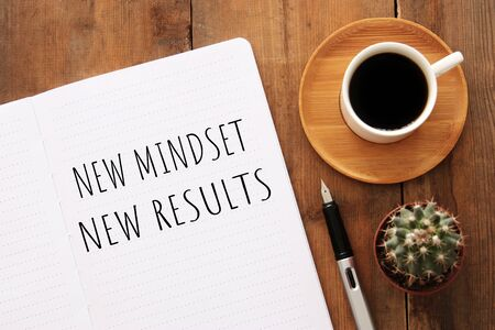 Top view image of table with open notebook and the text new mindset new results. Success and personal development concept Stock Photo