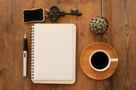 Open notebook with empty pages and other office supplies over wooden old office desk table. Top view, flat lay