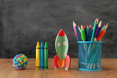 Istruzione e ritorno al concetto di scuola. Razzo di cartone e matite davanti alla lavagna dell'aula Archivio Fotografico