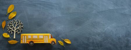 education and back to school. Top view photo of cardboard school bus next to autumn dry leaves over classroom blackboard background