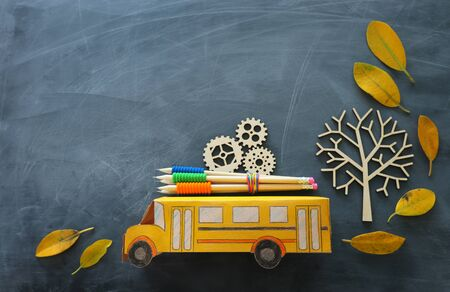 education and back to school concept. Top view photo of cardboard school bus, wooden gears as concept of success and achievement and pencils next to tree with autumn dry leaves over classroom blackboard background Stockfoto