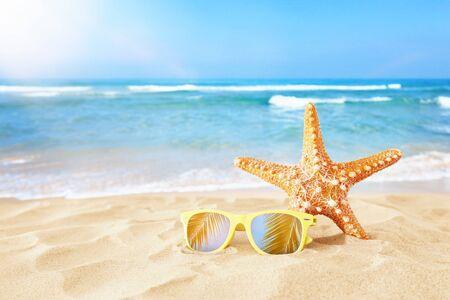 Wakacje. Piaszczysta plaża, okulary przeciwsłoneczne i rozgwiazda przed letnim tłem morza z miejscem na kopię
