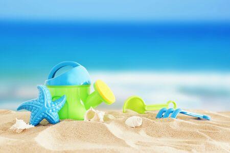 Urlaubs- und Sommerbild mit buntem Spielzeug des Strandes für Kinder über dem Sand