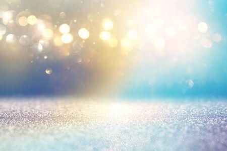 Abstract glitter lights background. Golden and light blue. De-focused