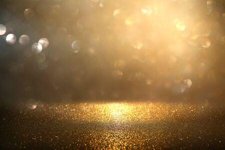 Glitter vintage lights background. Gold and black. De-focused.