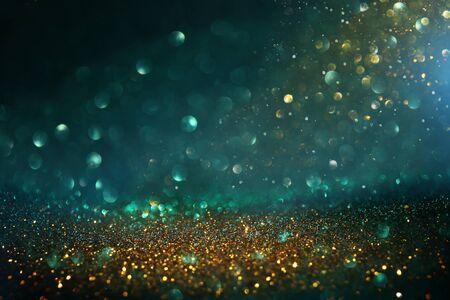 Abstrakter Glitter beleuchtet Hintergrund. Schwarz, Blau, Gold und Grün. Defokussiert