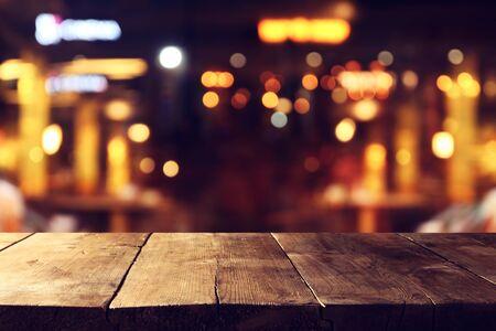 Fond de table en bois devant les lumières floues abstraites du restaurant