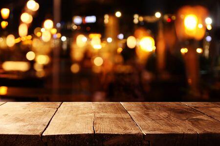 Tło drewnianego stołu przed abstrakcyjnymi niewyraźnymi światłami restauracji