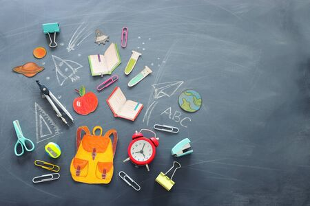 education and back to school concept. shapes cut from paper and painted of backpack, books, chemistry flask and apple over classroom blackboard with funny sketches. top view, banner