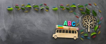 Education and back to school concept. Top view photo of wooden bus and ABC letters, pencils on the roof next to tree with autumn leaves over classroom blackboard background. Top view, flat lay Standard-Bild
