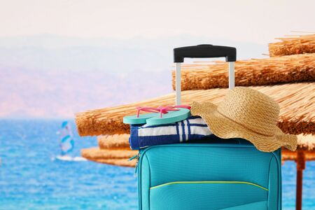 Holidays. Travel concept. Blue suitcase with female hat, flip flips and beach towel in front of tropical background Foto de archivo
