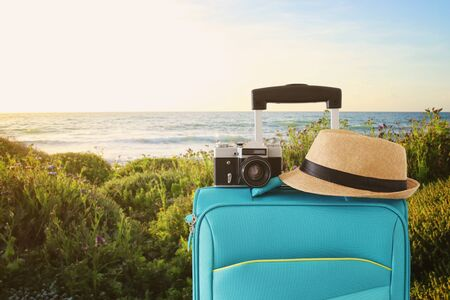 Recreation image of traveler luggage, camera and fedora hat infront of a rural lanscape. Holiday and vacation concept