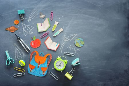 Education and back to school concept. Shapes cut from paper and painted of backpack, books, chemistry flask and apple over classroom blackboard with funny sketches. Top view, flat lay