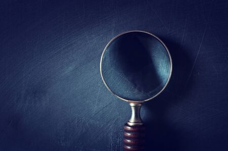 Vintage magnifying glass with wooden handle over chalkboard background. Top view, flat lay Reklamní fotografie