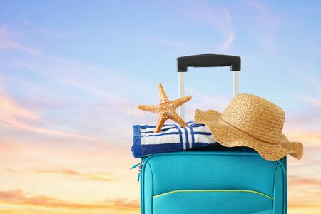 Holidays. Travel concept. Blue suitcase with female hat, starfish and beach towel in front of tropical sunset sky background 免版税图像
