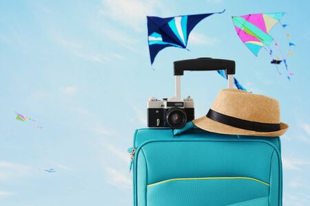 Recreation image of traveler luggage, camera and fedora hat infront of blue sty with flying colorful kites background. Holiday and vacation concept Stock Photo