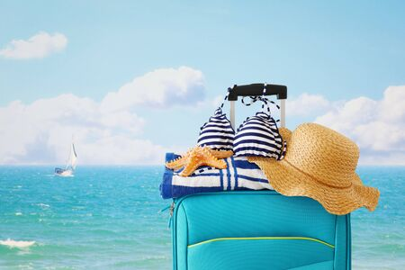 Holidays. Travel concept. Blue suitcase with female hat, starfish, bikini and beach towel in front of tropical background
