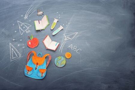Education and back to school concept. Shapes cut from paper and painted of backpack, books, chemistry flask and apple over classroom blackboard with funny sketches. Top view, flat lay Stockfoto