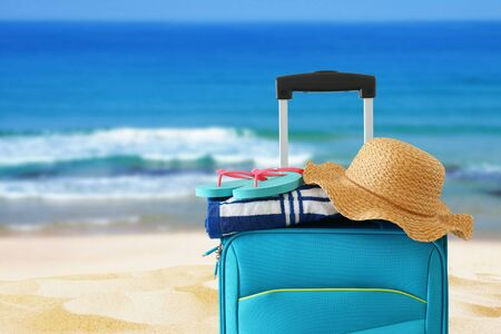 Holidays. Travel concept. Blue suitcase with female hat, flip flips and beach towel in front of tropical background