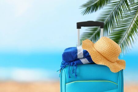 Holidays. Travel concept. Blue suitcase with female hat and beach towel infront of tropical background 版權商用圖片