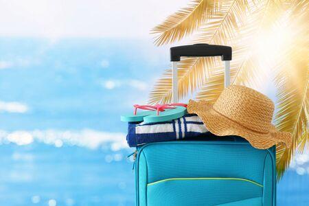 Días festivos. Concepto de viaje. Maleta azul con sombrero femenino, flip flips y toalla de playa frente a fondo tropical Foto de archivo