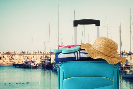 Holidays. Travel concept. Blue suitcase with female hat, flip flips and beach towel in front of marina with yachts background