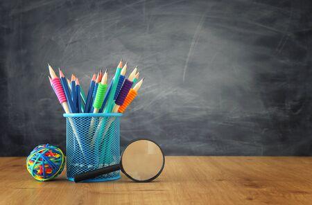 Edukacja i powrót do koncepcji szkoły. Artykuły papiernicze nad drewnianym stołem przed tablicą w klasie Zdjęcie Seryjne