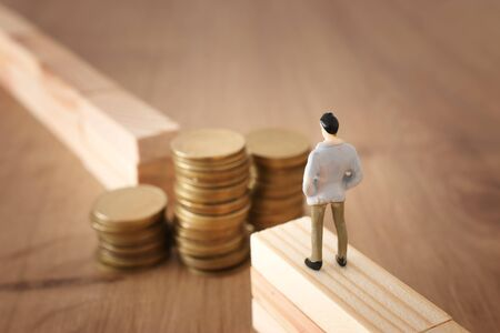 business concept image of challenge. A man stands on the edge of a gap and looks at a stack of coins, thinking how to earn more money