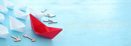 business. Leadership concept image with paper boats on blue wooden background. One leader guiding othes.